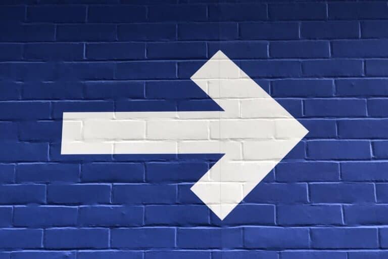 White arrow on a blue brick wall